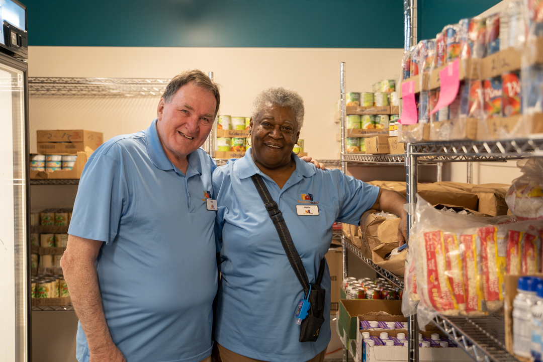 Caucasian male and african american woman posing for a picture in the Food Pantries at Senior Communities