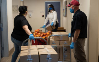 two hispanic females and one hispanic male working in the Golden Groceries at Senior Communities photo galleries