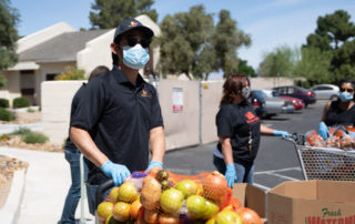 hispanic male pushing a cart of apples, potatoes, onion and avacados.