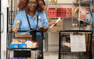 African american woman with brown hair pushing a shopping cart while shopping in the Food Pantries at Senior Communities